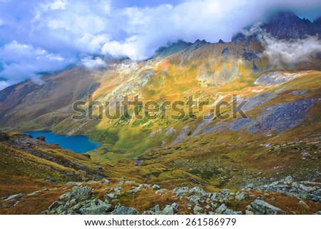 Bad weather in the mountains. Panoramic view over the lake. Picture was taken during trekking hike in scenic Caucasus mountains at autumn,Arhiz region, Abishira-Ahuba range, Karachay-Cherkessia,Russia - stock photo