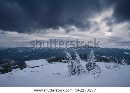 Bad weather in the mountains. Winter landscape. Cloudy evening with storm clouds. Wooden houses of shepherds under the snow. Carpathians, Ukraine, Europe - stock photo