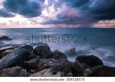 Bad weather. Stormy weather on the stone coast at sunset. Rain on the horizon. Long exposure