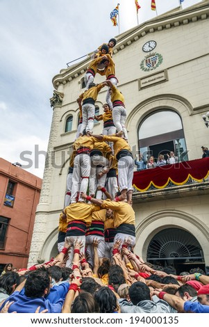 BADALONA, SPAIN- MAY 18, 2014: Some unidentified people called Castellers do a Castell or Human Tower, typical tradition in Catalonia. Castells were declared Intangible Cultural Heritage by UNESCO - stock photo