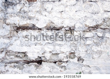 Badly decayed and peeling whitewashed wall - stock photo