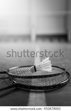 Badminton ball (shuttlecock) and racket on court floor. White color badminton ball. Two badminton racket. Badminton ball with selective focus. Black and white.