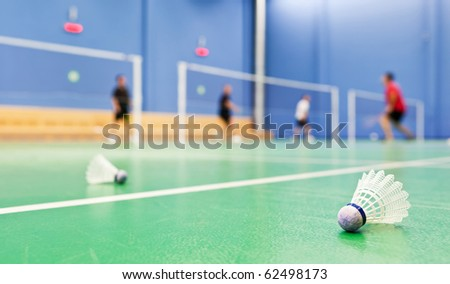 badminton - indoor badminton courts with players; shallow DOF, sharp focus on the shuttlecock in the foreground (color toned image) - stock photo