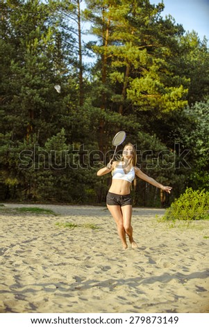 Badminton motion in a game with blond girl on sand beach