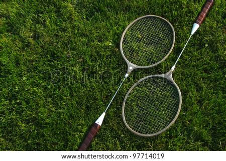 badminton racket set on green grass - stock photo