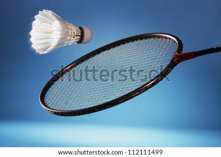 Badminton racket striking shuttlecock - stock photo