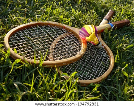 badminton rackets and shuttlecock in the grass - stock photo