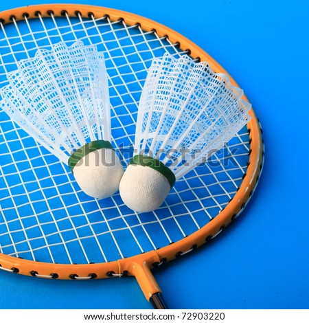 Badminton rackets and shuttlecock isolated on blue background - stock photo