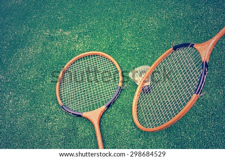 Badminton racquets and shuttlecock on green artificial grass, vintage look filters applied