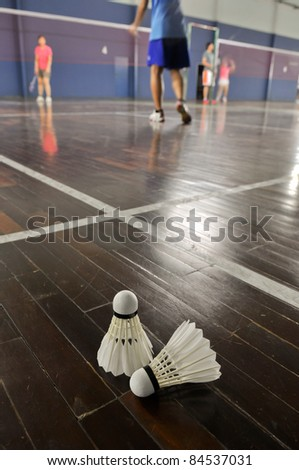 Badminton - two shuttlecocks in the badminton courts with player - stock photo