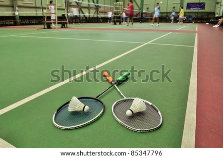Badminton - two shuttlecocks on rackets in the badminton courts - stock photo