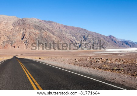 Badwater Road disappearing into barren Death Valley. - stock photo