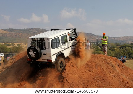 BAFOKENG - MAY 18: White Mercedes-Benz G-Class scaling steep sand hill obstacle at new 4x4 track opening event May 18, 2013 in Bafokeng, Rustenburg, South Africa