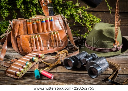 Bag, bullets and hat in a hunting lodge - stock photo