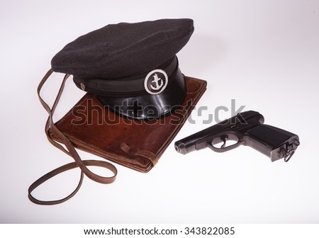 Bag cards, pistol and naval cap on a white background in studio  - stock photo