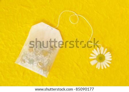Bag of chamomile tea over yellow handmade paper - concept - stock photo