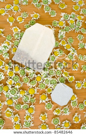 Bag of chamomile tea with dry chamomilla flowers over wooden background