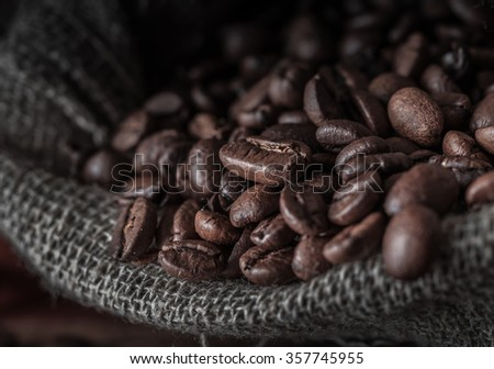 Bag of coffee beans on a dark background. Macro. Shallow depth of field. - stock photo