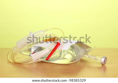 Bag of intravenous antibiotics and plastic infusion set on wooden table on green background - stock photo