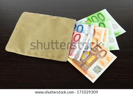 Bag of money with different euro banknotes on wooden background - stock photo