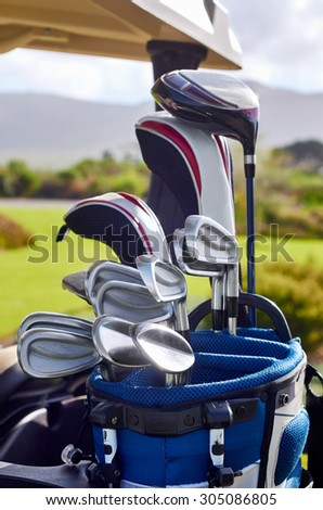 bag of various iron golf clubs on cart buggy - stock photo