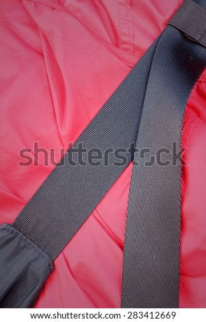 Bag strap on a red shirt of teenage - stock photo