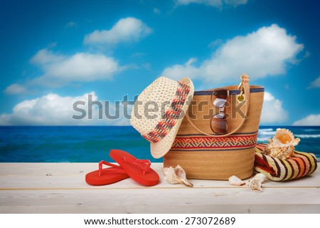 Bag, sunglasses, hat and flip flops on sea sky background - stock photo