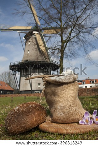 Bag with flour and bread with windmill background - stock photo