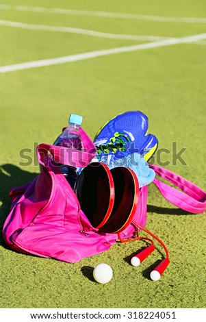 Bag with sports equipment on the sports courts background. Ping-pong ball (for table tennis), racket, rope, sneakers, bottle of water, towel. Concept - sport, leisure, healthy lifestyle. Copy space. - stock photo