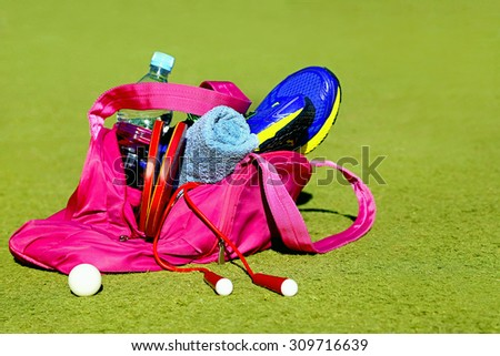 Bag with sports equipment on the sports courts. Ping-pong ball (for table tennis), racket, rope, sneakers, bottle of water, towel. Concept about activity, sport, healthy lifestyle. Copy space. - stock photo
