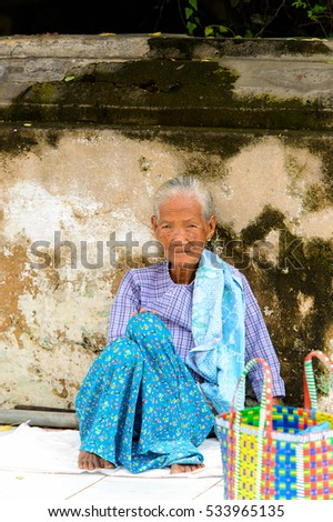 BAGAN, MYANMAR - AUG 29, 2016: Unidentified Burmese old lady sits on the ground. 68 per cent of  Myanma people belong to Bamar ethnic group