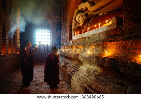 BAGAN, MYANMAR - Dec 11: Monk is praying with candles in front of Buddha statue inside pagoda on Dec 11, 2015 in Bagan. Monks with light and Buddha are highlighted of Bagan.