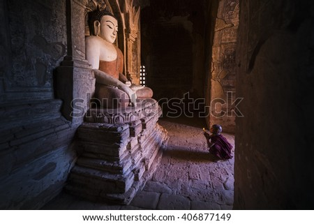 BAGAN, MYANMAR - DEC 17, 2014: Neophyte praying with candle light in a Buddihist temple on December 17, 2014 in Bagan, Myanmar. - stock photo