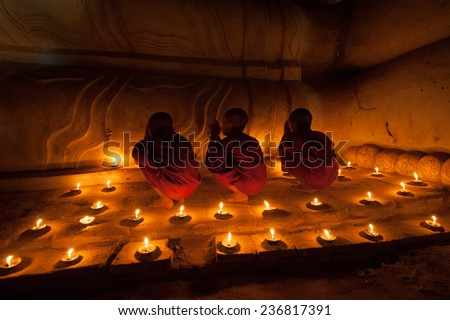 BAGAN, MYANMAR - DEC 31, 2012: Southeast Asian young little Buddhist monks praying with candle light in a Buddihist temple on December 31, 2012  in Bagan, Myanmar.  - stock photo