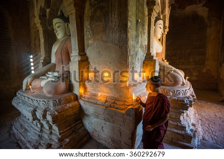 BAGAN, MYANMAR - DEC 12, 2015: Unidentified Buddhism neophyte prays to the Buddha in Buddihist temple on December 12, 2015 in Bagan, Myanmar. Southeast Asian neophyte praying in a Buddihist temple - stock photo