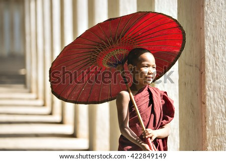 BAGAN, MYANMAR - DEC 6: Unidentified young Buddhism novice at Shwezigon temple holding an umbrella on Dec 6, 2014 in Bagan.  - stock photo