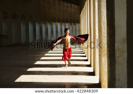 BAGAN, MYANMAR - DEC 6: Unidentified young Buddhism novice is running at Shwezigon temple on Dec 6, 2014 in Bagan.  - stock photo