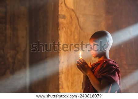 BAGAN, MYANMAR - DEC 6: Unidentified young Buddhism novice pray on Dec 6, 2014 in Bagan. Buddhism is predominantly of the Theravada tradition, practised by 89% of the population. - stock photo