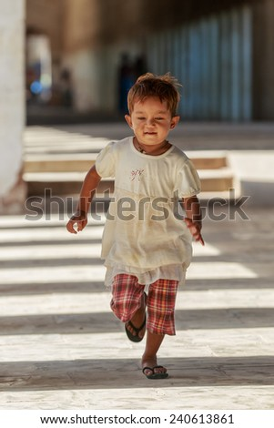 BAGAN, MYANMAR - DEC 6: Unidentified young kid at Shwezigon temple on Dec 6, 2014 in Bagan. Myanmar is a source country for children who are subjected to human trafficking, specifically forced labor. - stock photo