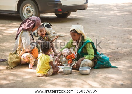 BAGAN, MYANMAR - DECEMBER 10 : The unidentified beggar family are waiting  for money from tourists  in pagoda valley on December 10, 2015 in Bagan,Myanmar