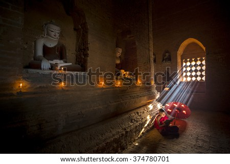 BAGAN, MYANMAR - FEB 20: Unidentified young Buddhism reading scripture in old temple on FEB 20, 2015 in Bagan. Buddhism is predominantly of the Theravada tradition, practised by 89% of the population - stock photo