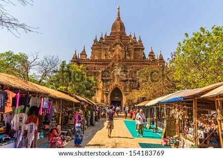 BAGAN, MYANMAR - FEBRUARY 22: Htilominlo Temple entrance with tourist passing by street market to enter the temple on February 22, 2013 in Bagan, Myanmar. - stock photo
