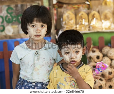 BAGAN, MYANMAR-FEBRUARY 19, 2015 : Unidentified childrens demonstrates the use of Thanaka, a yellowish-white paste made from ground bark & used as a cosmetic and for sunburn protection. - stock photo