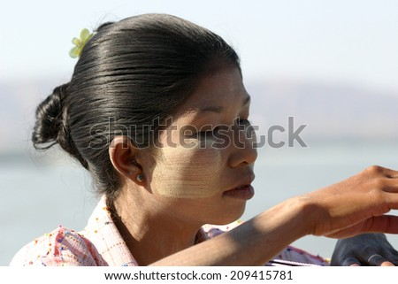 BAGAN, MYANMAR:  JAN. 4:  A Burmese woman models thanaka, a cosmetic paste made from ground bark which is used as an insect repellent, sunscreen and cosmetic on January 4, 2010. - stock photo