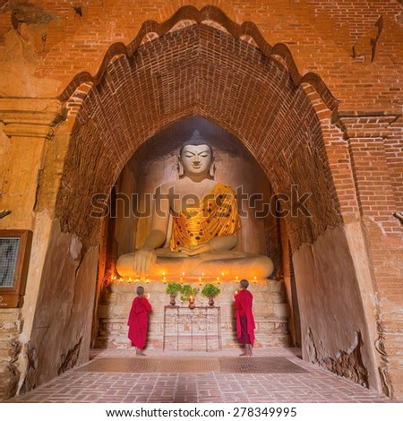 BAGAN, MYANMAR - JAN 16, 2015: Southeast Asian neophyte praying with candle light in a Buddihist temple on January 16, 2015 in Bagan, Myanmar. - stock photo