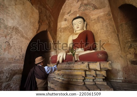 BAGAN, MYANMAR - 14 JAN, 2014: Unidentified Burmese man brings religious offerings to Buddha statue inside one of pagoda ruins at Bagan Kingdom, Myanmar (Burma) - stock photo