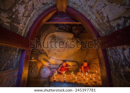 BAGAN, MYANMAR - JAN 15,2015: Unidentified young Buddhism monks praying with candle light at Shwesandaw temple on January 15, 2015 in Bagan, Myanmar.  - stock photo