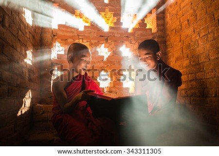 BAGAN, MYANMAR - NOVEMBER 22, 2015: Southeast Asian neophytes  are reading  and funny in a Buddihist temple on November 22, 2015 in Bagan, Myanmar. - stock photo