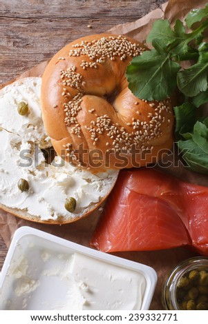 Bagel and ingredients: fish, cheese, capers on the table close-up. vertical top view  - stock photo