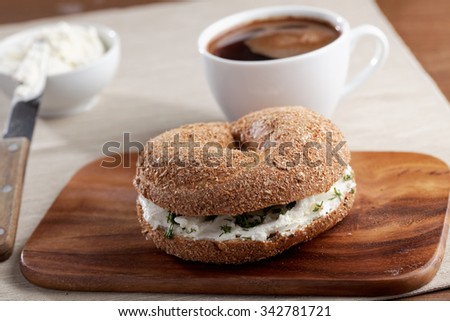 Bagel sandwich with cream cheese and parsley on a wooden cutting board - stock photo